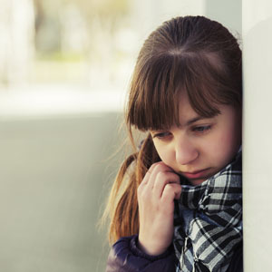 463146837 - Teenage girl in depression at the wall